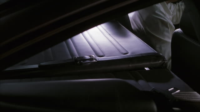 medium angle of metal briefcase in car compartment. see hand from seat in front reach back, open briefcase and grab machine gun out. - briefcase stock videos & royalty-free footage