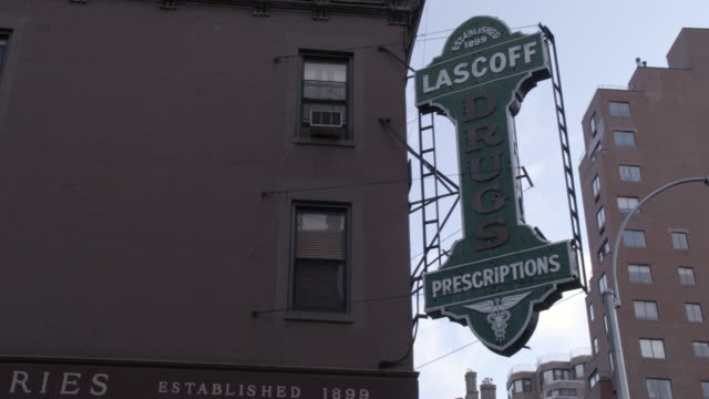 """pan down from """"lascoff drugs"""" sign to pharmacy entrance with awning on the street corner of lexington avenue and 82nd street. - awning stock videos & royalty-free footage"""
