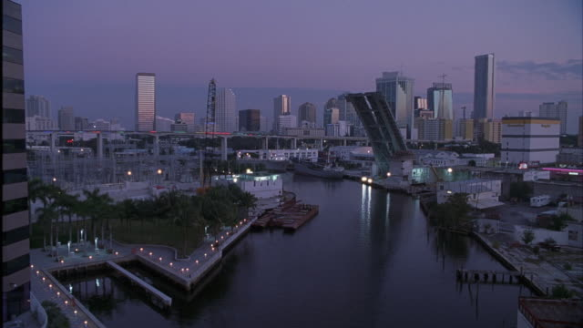 est wide angle of miami skyline. dusk. see canal running through middle of shot. drawbridge is up over canal. - drawbridge stock videos and b-roll footage