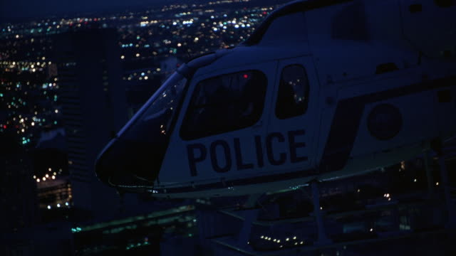 air-to-air aerial of police helicopter flying above downtown miami. see bank of america tower pass by below. helicopter tilts and then flies off into downtown, away from camera. night. - helicopter stock videos & royalty-free footage