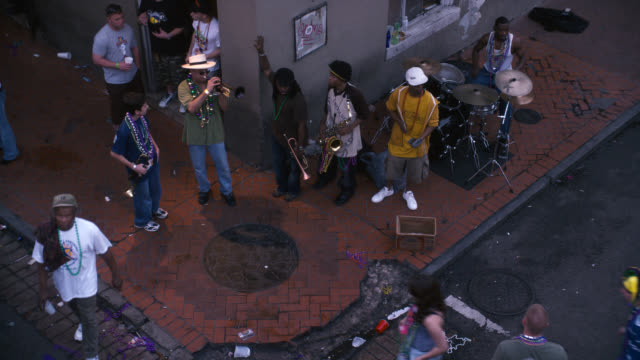 high angle down of band or group of musicians on city street corner. celebration, party or festival. mardi gras, could be bourbon street. - new orleans mardi gras stock videos and b-roll footage