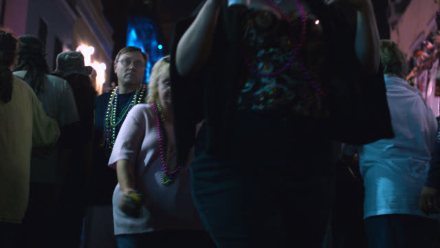 medium angle of people or pedestrians in city street, bourbon street. crowds. party, festival, celebration, mardi gras. - mardi gras stock videos and b-roll footage