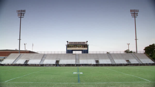 wide angle of empty football stadium and field. could be at high school. bleachers or stands in bg. - アメリカンフットボール場点の映像素材/bロール