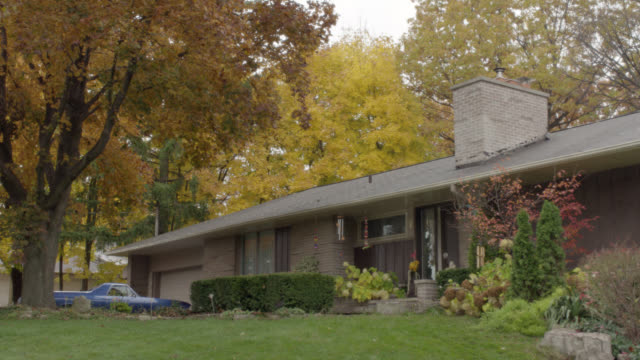 WIDE ANGLE OF SUBURBAN RANCH HOUSE WITH CHIMNEY AND FRONT YARD SHRUBBERY. WIND CHIMES, LARGE TREES WITH AUTUMN LEAVES VISIBLE. TRUCK PARKED BY GARAGE. OVERCAST SKY.