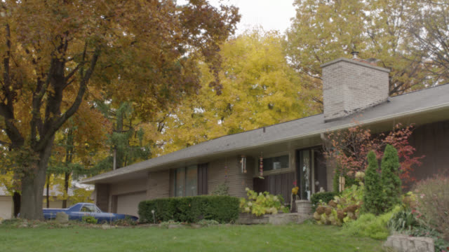 WIDE ANGLE PAN UP TO SUBURBAN RANCH HOUSE WITH CHIMNEY AND FRONT YARD SHRUBBERY. WIND CHIMES, LARGE TREES WITH AUTUMN LEAVES VISIBLE. TRUCK PARKED BY GARAGE. OVERCAST SKY. FRONT DOOR CLOSES THEN OPENS.