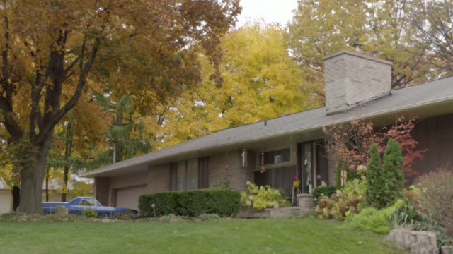WIDE ANGLE OF SUBURBAN RANCH HOUSE WITH CHIMNEY AND FRONT YARD SHRUBBERY. WIND CHIMES, LARGE TREES WITH AUTUMN LEAVES VISIBLE. FRONT DOOR OPENS. TRUCK PARKED BY GARAGE. OVERCAST SKY.