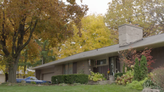 wide angle of suburban ranch house with chimney and front yard shrubbery. wind chimes, large trees with autumn leaves visible. front door closes then opens. truck parked by garage. overcast sky. - ontario canada stock videos and b-roll footage
