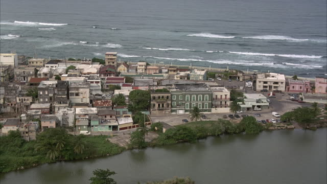 aerial, coastal town.  see rooftops of houses and buildings, see delta leading to ocean. see ocean in background. could be any central american coastal town. - カリブ海点の映像素材/bロール
