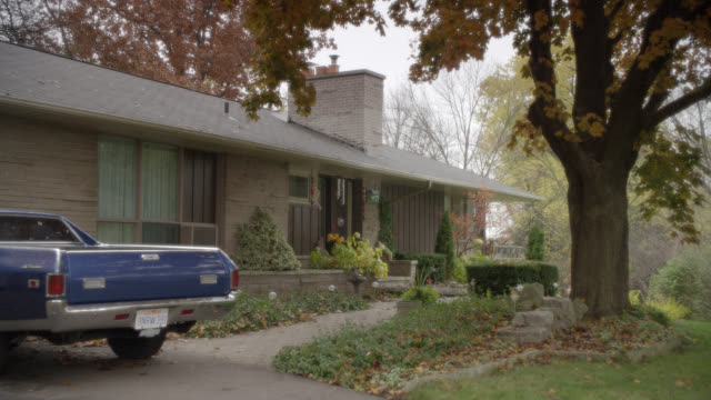 WIDE ANGLE OF SUBURBAN OR RURAL RANCH HOUSE WITH CHIMNEY AND FRONT YARD SHRUBBERY. WIND CHIMES, LARGE TREES WITH AUTUMN LEAVES VISIBLE. PICKUP TRUCK PARKED BY GARAGE. OVERCAST SKY.