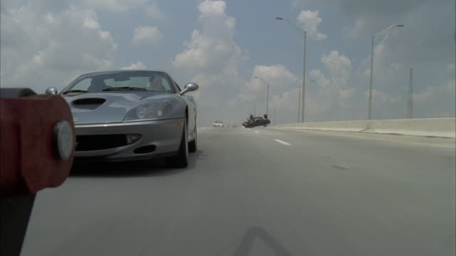 stockvideo's en b-roll-footage met medium angle, pov under moving car on highway. see car released, flip onto highway.  see silver ferrari 575m maranello enter frame, drive behind pov. see police cars follow, bizbars flashing in background. see highway, buildings in background. see ferrari - auto ongeluk