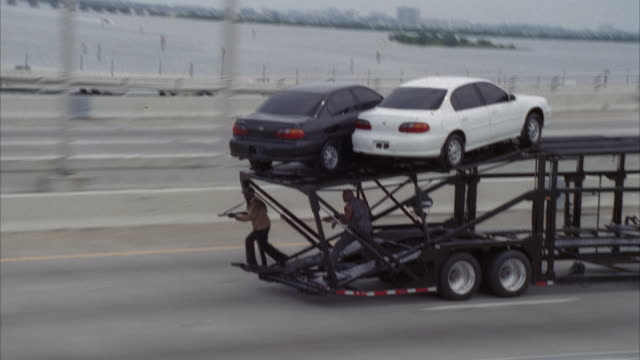 zoom in on car transport truck driving on highway. see two men shooting machine guns on back of truck. see black car released from top of transport. - see other clips from this shoot 2236 stock-videos und b-roll-filmmaterial