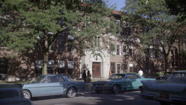 stockvideo's en b-roll-footage met wide angle of students carrying books and entering red brick school building. parked classic cars, including ford mustang visible in fg. - school building