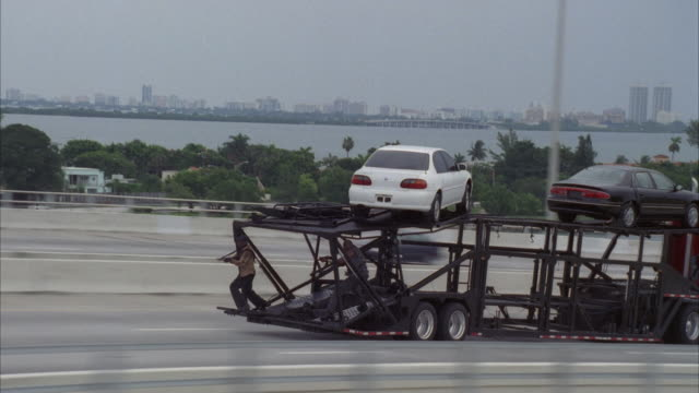 medium angle, black car crashing on highway. pan right to see car transport truck with two men shooting machine guns from the back. see water and skyline in background. - see other clips from this shoot 2236 stock-videos und b-roll-filmmaterial