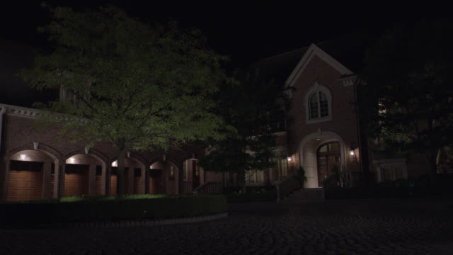 wide angle of red brick estate or mansion with cobblestone circular driveway, 4 car garage. arches, trees, lit entrance visible. - back lit video stock e b–roll