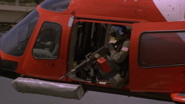AERIAL. MEDIUM ANGLE OF SOLDIER FIRING MACHINE GUN  FROM FLYING COAST GUARD HELICOPTER. SOLDIER IS AIMING DOWN. ZOOMS IN ON SOLDIER. PANS UP PAST HELICOPTER BLADES AT END.