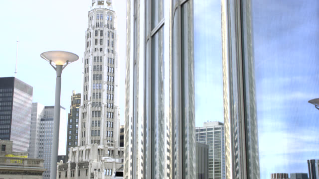 wide angle of tribune tower in reflection of high rise office building window in downtown chicago. landmarks. american flag visible on top of tower. - tribune tower stock-videos und b-roll-filmmaterial