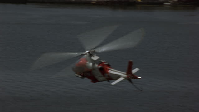 AERIAL POV FOLLOWS COAST GUARD HELICOPTER RIGHT TO LEFT OVER WATER. SEE CRUISE SHIP IN BACKGROUND.