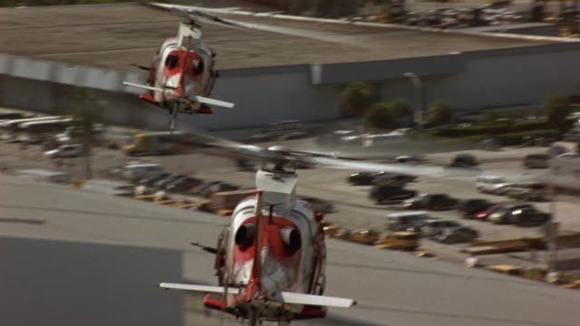 AERIAL POV FOLLOWS TWO COAST GUARD HELICOPTERS, ONE POLICE HELICOPTER FLYING OVER HARBOR. HELICOPTERS FLY PAST CRUISE SHIP, OVER SHIPYARD.