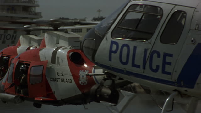 AERIAL POV FOLLOWS TWO COAST GUARD HELICOPTERS, ONE POLICE HELICOPTER FLYING PAST CRUISE SHIP. SEE SOLDIERS WITH MACHINE GUNS IN OPEN DOORS.