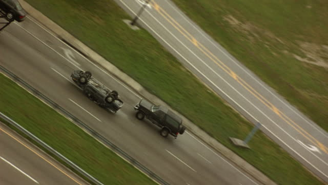 AERIAL, SEE FLIPPED CAR ATTACHED TO CAR TRANSPORT TRUCK BY CABLE, DRAGGING ON HIGHWAY RIGHT TO LEFT. FORD BRONCO IN RIGHT LANE CHASES CAR AND TRANSPORTER TRUCK. ZOOM IN, PAN RIGHT TO LEFT, SEE TRANSPORTER WITH CARS ON BOTH LEVELS.