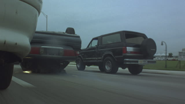 vídeos de stock e filmes b-roll de medium angle overturned buick dragged on highway, sparks flying. see car in left lane, ford bronco in right on either side of buick. buick attached to car transport truck by cable. see ford bronco crash into side of buick. buick crashes into car on left. - cable