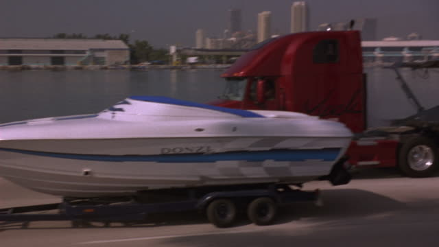 MEDIUM ANGLE, POV FOLLOWS RED MACK TRUCK. MACK TRUCK DRIVES ALONGSIDE TRUCK TOWING MOTORBOAT. SEE TWO TRUCKS COLLIDE. SEE HIGH RISES, HARBOR, WAREHOUSE IN BACKGROUND