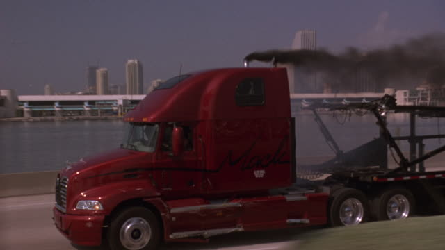 MEDIUM ANGLE, POV FOLLOWS RED MACK TRUCK. SEE POLICE CARS, BIZBARS FLASHING BEHIND TRUCK. MACK TRUCK DRIVES ALONGSIDE TRUCK TOWING MOTORBOAT. SEE TWO TRUCKS COLLIDE, SPARKS FLY. SEE HIGH RISES, HARBOR, WAREHOUSE IN BACKGROUND