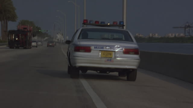 medium angle,  driving pov follows miami police car, bizbars flashing. see car transport truck driving ahead of police car. see harbor frame right. see car wreck near guardrails to left. - police car stock videos and b-roll footage