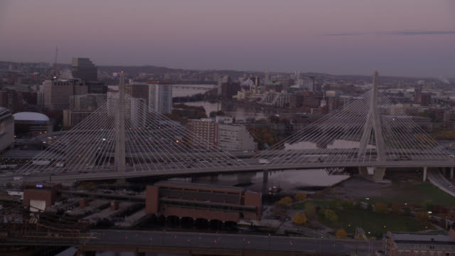 aerial of zakim  bridge over charles river in boston. city skyline with high rise office or apartment buildings visible in bg. - river charles stock videos & royalty-free footage