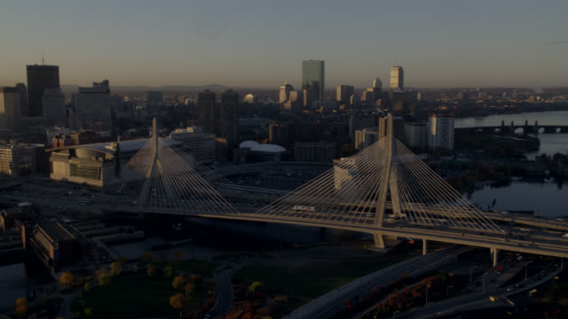 AERIAL OF ZAKIM BRIDGE OVER CHARLES RIVER IN BOSTON. TD GARDENS SPORTS ARENA VISIBLE NEXT TO BRIDGE. CARS DRIVE ON BRIDGE, FREEWAY, AND HIGHWAY. BOSTON SKYLINE VISIBLE IN BG. HIGH RISE OFFICE OR APARTMENT BUILDINGS.