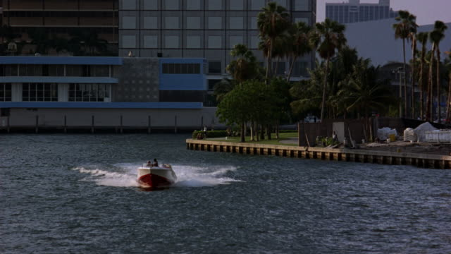 wide angle of red and white motorboat speeding toward camera through miami harbor or marina. three men in motorboat, and one man look over his shoulders multiple times. downtown miami skyline in background. could be part of boat chase. - {{ contactusnotification.cta }} stock-videos und b-roll-filmmaterial