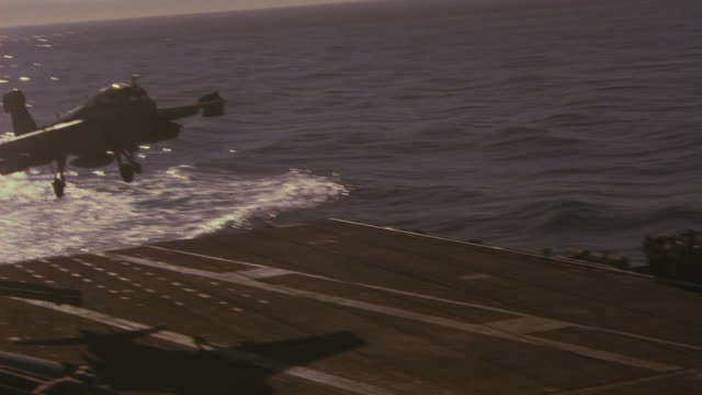 HAND HELD OF EA-6B PROWLER RECONNAISSANCE JET LANDING ON DECK OF NAVY AIRCRAFT CARRIER. MILITARY PERSONNEL VISIBLE ON DECK. RADAR ANTENNAS VISIBLE. WAVES OF PACIFIC OCEAN VISIBLE IN BG.