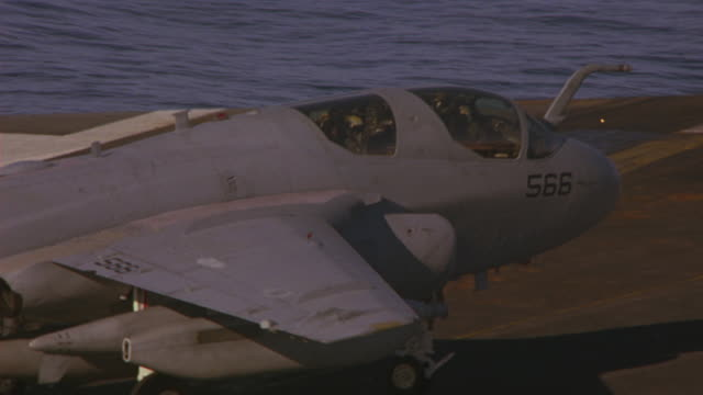 HAND HELD OF EA-6B PROWLER TAXIING AND PARKING ON DECK OF NAVY AIRCRAFT CARRIER. PILOT AND NAVIGATOR VISIBLE. WINGS FOLD. WAVES OF PACIFIC OCEAN VISIBLE IN BG.