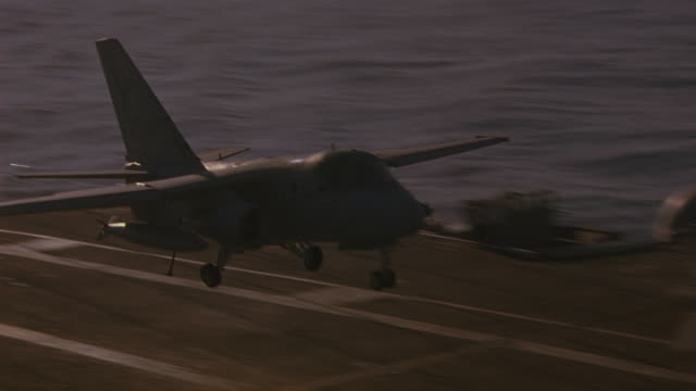 HAND HELD OF S-3B VIKING MILITARY JET LANDING ON DECK OF NAVY AIRCRAFT CARRIER.  MILITARY PERSONNEL VISIBLE ON DECK. RADAR ANTENNAS VISIBLE. WAVES OF PACIFIC OCEAN VISIBLE IN BG.