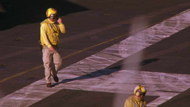 HAND HELD OF S-3B VIKING MILITARY JET ON DECK OF NAVY AIRCRAFT CARRIER. WINGS FOLD AND JET TURNS TOWARD CAMERA. PILOT AND FLIGHT OFFICER VISIBLE IN COCKPIT. MILITARY PERSONNEL MOVE AND WORK ON DECK. WAVES OF PACIFIC OCEAN VISIBLE IN BG.