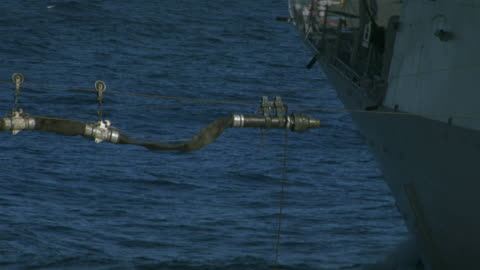 vídeos y material grabado en eventos de stock de zoom in on a hose being used to refuel a navy ship or cruiser, pulled by a rope. military personnel watch. could be used to show how the military needs fuel or oil. pov from aircraft carrier. - echar combustible