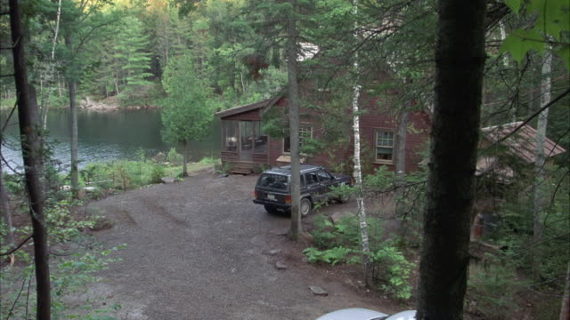 stockvideo's en b-roll-footage met est wide angle of brown cabin surrounded by trees on lake. gray jeep cherokee in gravel driveway. - grind