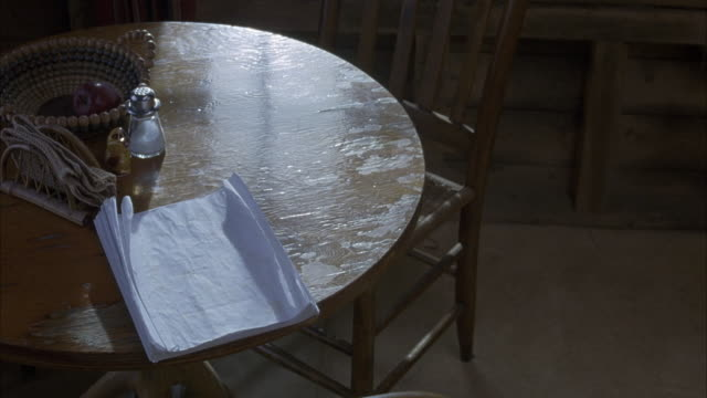 close angle. stack of papers on wooden table. bowl, napkin holder and salt and pepper shakers on table as well. papers appear to be a script - napkin stock videos & royalty-free footage