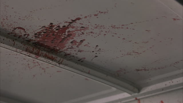 vídeos de stock, filmes e b-roll de medium angle insert of blood splattered on white roof of car. - sangue