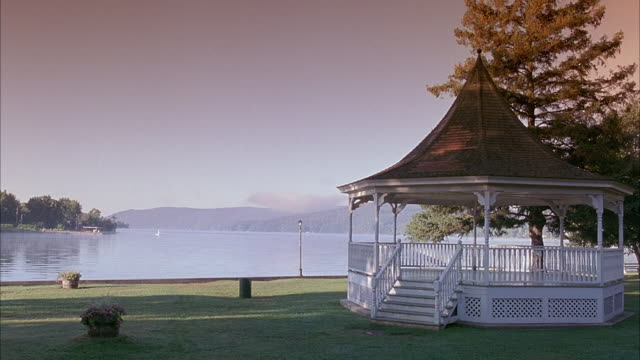 est wide angle of lake. gazebo in foreground in park. - gazebo stock videos & royalty-free footage