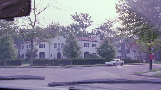 wide angle driving pov straight forward of two story houses and mansions in upper middle class neighborhood. car turns right at intersection in residential area. streets. - middle class stock videos & royalty-free footage