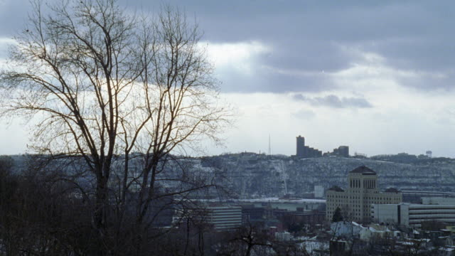 vídeos y material grabado en eventos de stock de zoom in on allegheny general hospital. multi-story buildings could be government buildings, office buildings, or hotels. building on hill. bare tree in foreground. clouds. snow. - bare tree