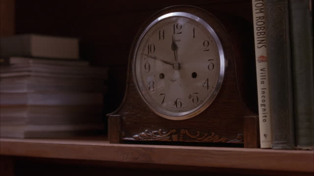 "est close angle shot of mantle clock on a bookshelf next to books. clock reads 10 minutes until 12. ""tom robbins' villa incognito"" book sits next to clock. - shelf stock videos and b-roll footage"