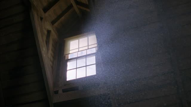 medium angle. looking up at window in attic. light shining through window. dust particles floating in light beam. shot gets darker at times. - vindsvåning bildbanksvideor och videomaterial från bakom kulisserna