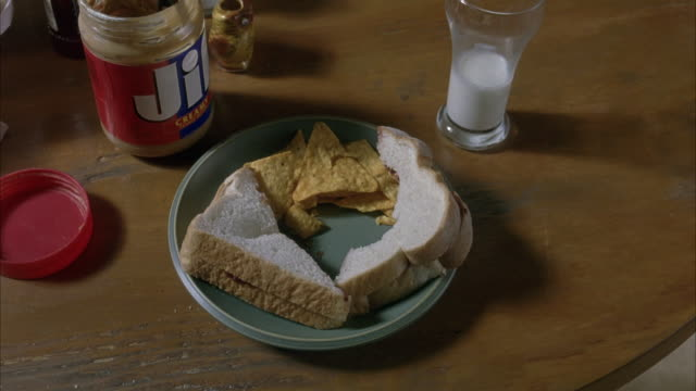 medium angle shot of partly eaten peanut butter and jelly sandwich on a plate.  some tortilla chips are also on the plate.  a half-full glass of milk and open can of jif peanut butter are next to the plate on the wooden table. - sandwich stock videos & royalty-free footage