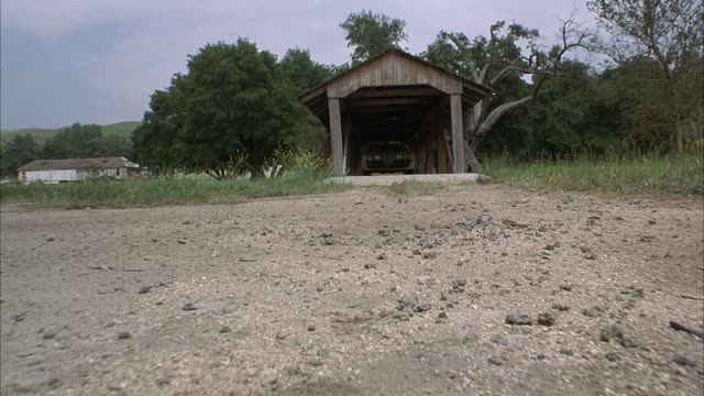 medium low angle - covered bridge.  1979 pontiac firebird trans am car comes out of bridge toward camera and skids as it turns quickly. set in countryside. - anno 2001 video stock e b–roll