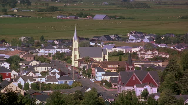 wide angle overlooking town of santa paula. small rural town. see main street running through town. tall church building in middle of main street. hills and grass fields in background. - anno 2001 video stock e b–roll