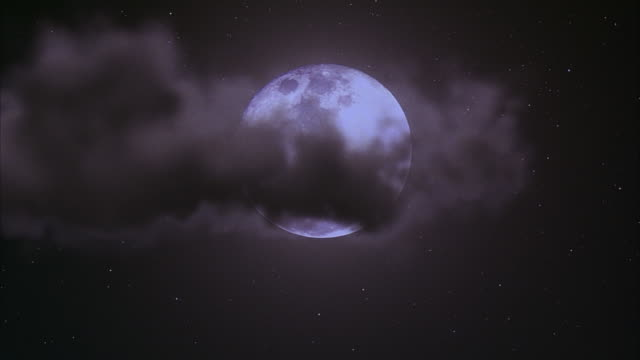medium angle of bright full moon with black clouds passing in front. black sky dotted with stars in background. - luna video stock e b–roll