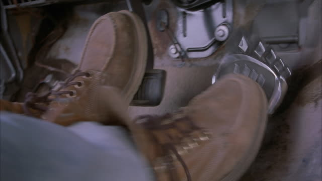 close angle of brown work boots stepping on gas pedal in a truck.  pedal shaped like a foot. camera tilts up to eight-track or 8-track player and down to feet. driving. - pedal stock videos & royalty-free footage