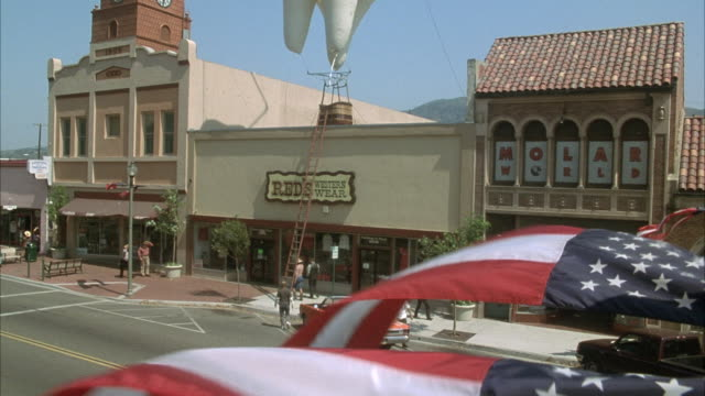 """vídeos y material grabado en eventos de stock de wide angle of main street in santa paula. american flag waves in foreground. buildings line sidewalk across street. see """"red's western wear"""" building. clock tower to left. see large hot air balloon shaped as tooth on roof of building. see man climb up lad - señal de nombre de calle"""